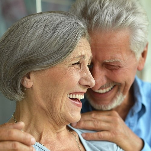 A laughing older couple to represent the convenience she provides at her Renton dental office.