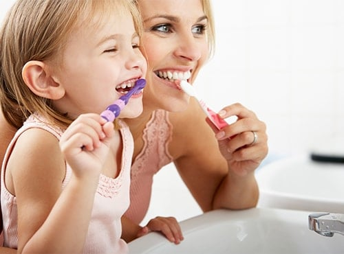 A mother and daughter brush to show the importance of regular dental care.
