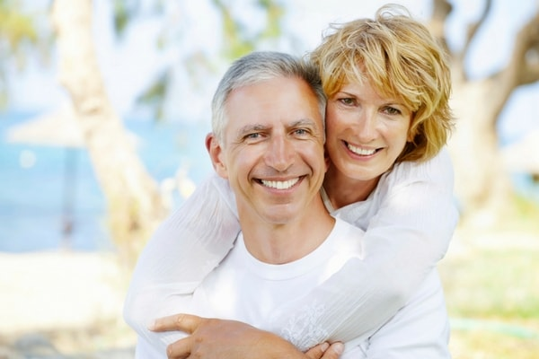 A mature couple embracing and smiling because they restored their missing teeth with dental implants in Renton, WA