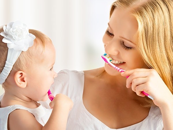 A baby daughter and her mom brushing their teeth together - a part of dental hygiene in our Renton dental office