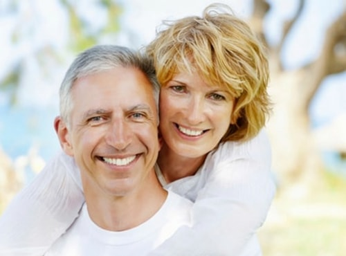 A lovely older couple smiling at the camera, showing off their new smile thanks to dental implants - Dentist Renton WA