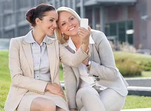 Two businesswomen take a selfie to show how teeth whitening can dramatically improve your smile.