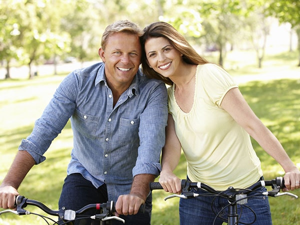A smiling couple bicycling outside - free from tooth pain, thanks to root canal therapy in Renton, WA