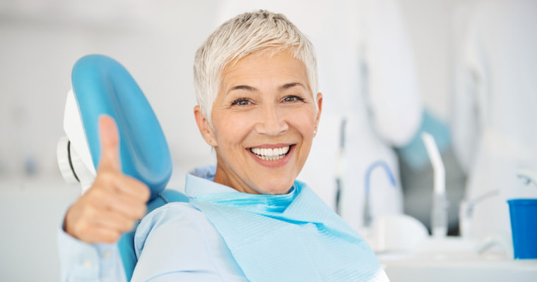 Dental implants patient with a thumbs up about being a good dental implants candidate